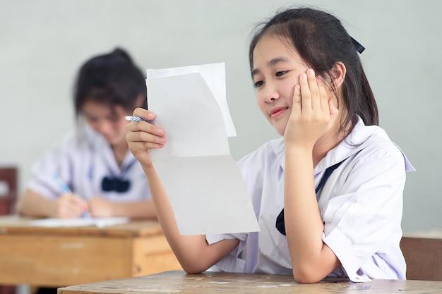Glimlach jong meisje student lezen en schrijven examen zonder stress.
