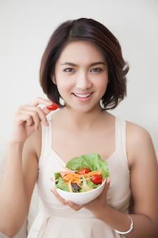 Glimlach jonge mooie vrouwen die een kom salade en tomaat houden