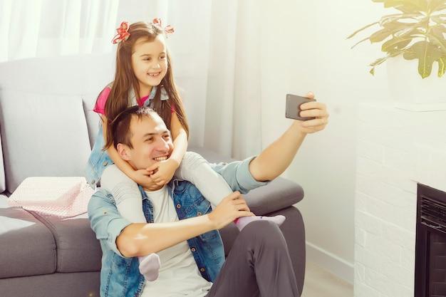 Glimlach! jonge vader en zijn kleine dochter die selfie nemen terwijl thuis het zitten op vloer