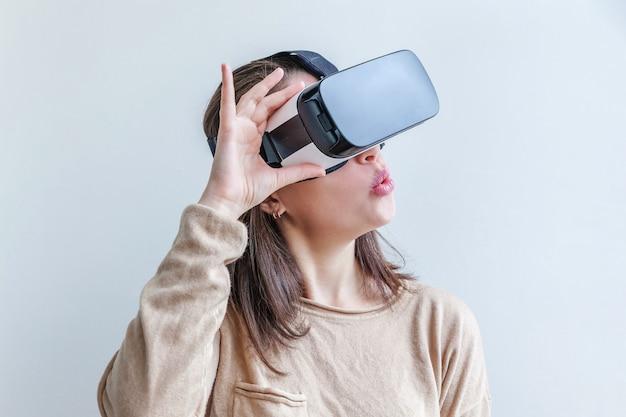 Glimlach jonge vrouw die gebruikend de virtuele hoofdtelefoon van de de glazenhelm van werkelijkheidsvr op wit dragen. smartphone gebruikt met virtual reality-bril. technologie, simulatie, hi-tech, videogameconcept.