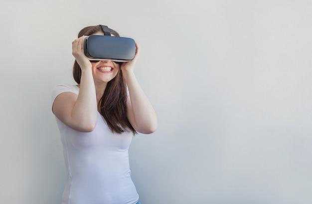 Glimlach jonge vrouw dragen met behulp van virtual reality vr bril helm headset op wit