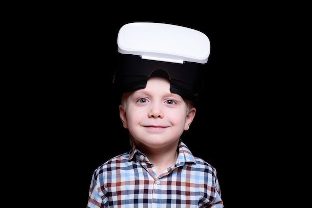 Glimlach jongetje met een bril van virtual reality. geruite overhemd.