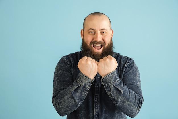 Glimlach. knappe blanke man portret geïsoleerd op blauwe muur met copyspace. stijlvol mannelijk model met baard. concept van menselijke emoties, gezichtsuitdrukking, verkoop, advertentie, mode, jeugd.