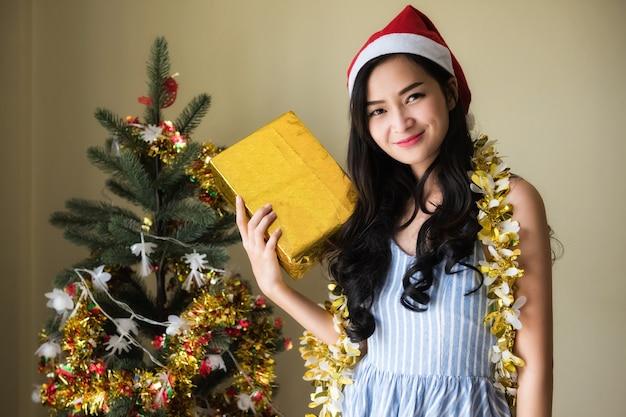 Glimlach schoonheid aziatische vrouw met kerstman hoed houdt gouden kerstcadeau doos van vriendje in de buurt van de kerstboom. gelukkig meisje viert nieuwjaar en kerstmis 2021.