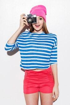 Glimlach! speelse jonge vrouw in funky kleding die door een camera kijkt terwijl ze tegen een witte achtergrond staat