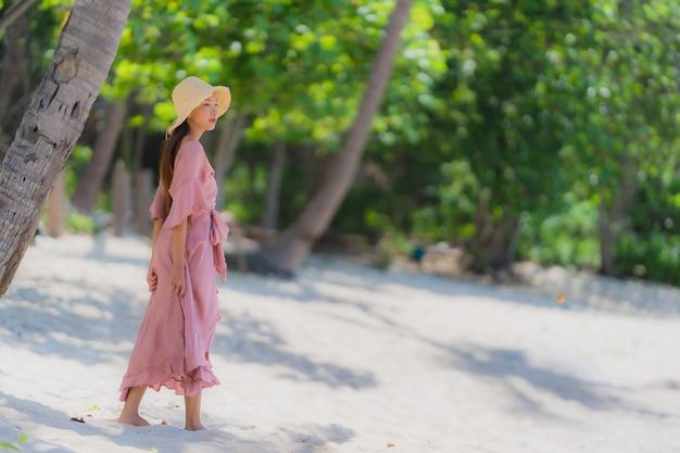 Glimlach van de portret de jonge aziatische vrouw gelukkig rond strand overzeese oceaan met kokosnotenpalm voor vakantievakantie