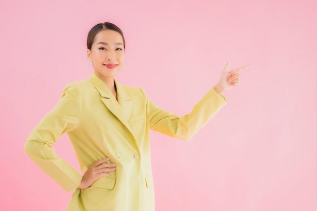 Glimlach van de portret de mooie jonge aziatische bedrijfsvrouw in actie op roze kleur