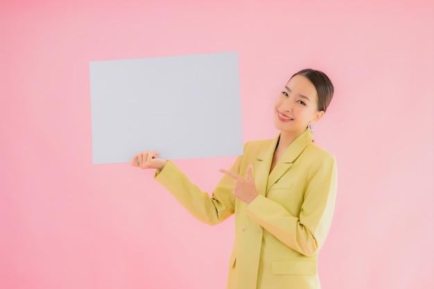 Glimlach van de portret de mooie jonge aziatische bedrijfsvrouw met lege witte aanplakbordkaart op kleur