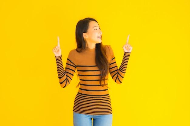Glimlach van de portret de mooie jonge aziatische volwassen vrouw met vele actie betreffende gele muur
