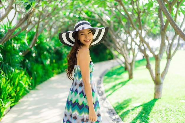 Glimlach van de portret de mooie jonge aziatische vrouw en gelukkige rond openluchttuin