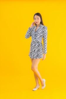 Glimlach van de portret de mooie jonge aziatische vrouw gelukkig met actie betreffende geel