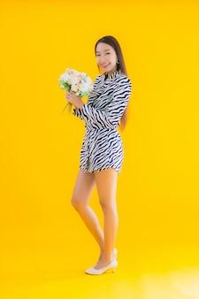 Glimlach van de portret de mooie jonge aziatische vrouw gelukkig met bloem op geel