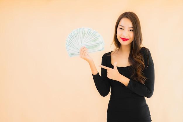 Glimlach van de portret de mooie jonge aziatische vrouw gelukkig met geld en contant geld
