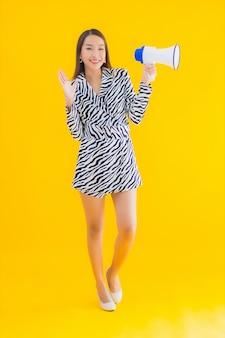 Glimlach van de portret de mooie jonge aziatische vrouw gelukkig met megafoon op geel