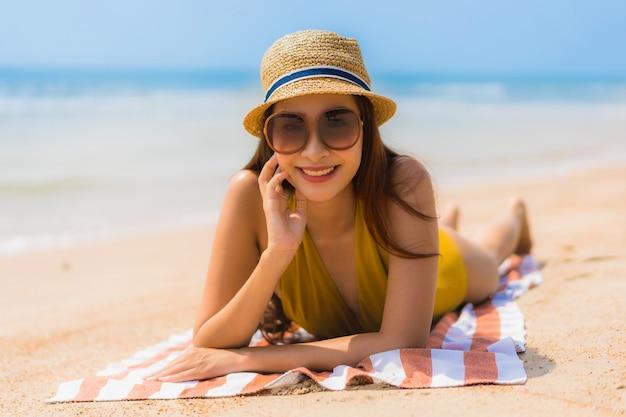 Glimlach van de portret de mooie jonge aziatische vrouw gelukkig op het strand en het overzees