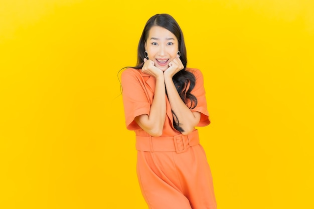Glimlach van de portret de mooie jonge aziatische vrouw met actie op geel