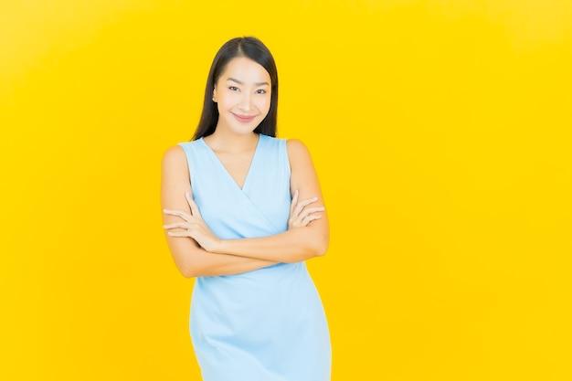 Glimlach van de portret de mooie jonge aziatische vrouw met actie op gele kleurenmuur