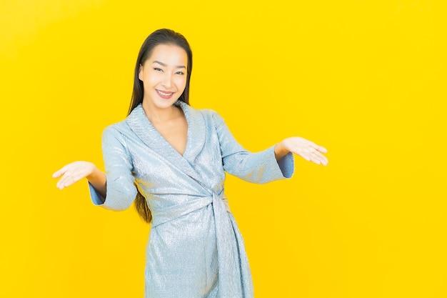 Glimlach van de portret de mooie jonge aziatische vrouw met actie op gele muur