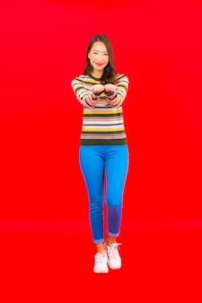 Glimlach van de portret de mooie jonge aziatische vrouw met actie op rode geïsoleerde muur