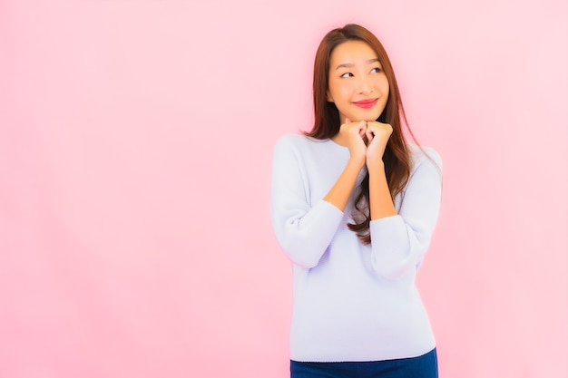 Glimlach van de portret de mooie jonge aziatische vrouw met actie op roze geïsoleerde muur