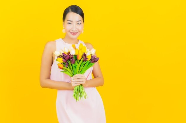 Glimlach van de portret de mooie jonge aziatische vrouw met bloem op geel