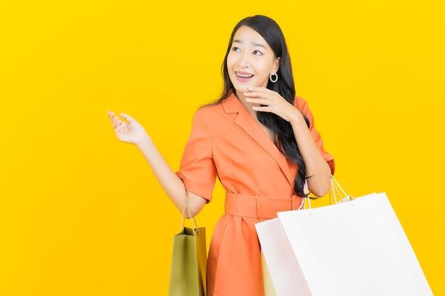 Glimlach van de portret de mooie jonge aziatische vrouw met boodschappentas op geel