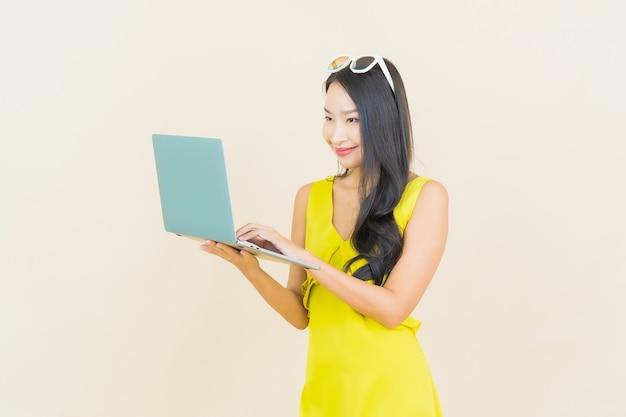 Glimlach van de portret de mooie jonge aziatische vrouw met computerlaptop op geïsoleerde muur