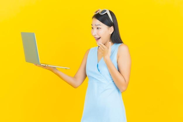 Glimlach van de portret de mooie jonge aziatische vrouw met computerlaptop op gele geïsoleerde muur