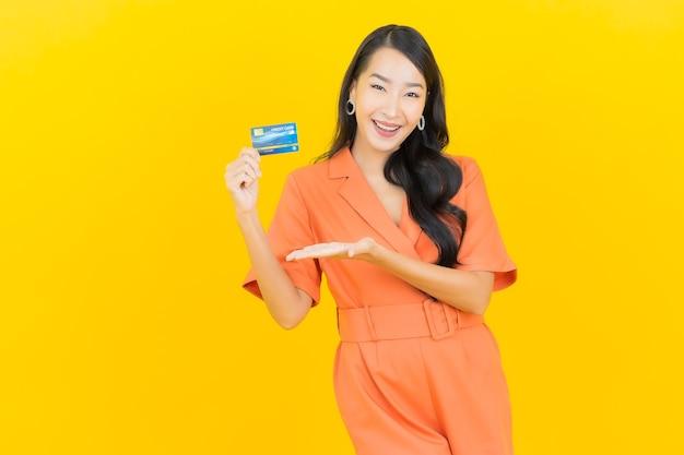 Glimlach van de portret de mooie jonge aziatische vrouw met creditcard op geel