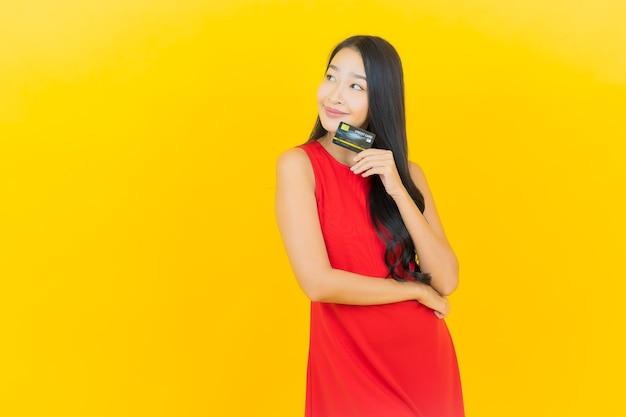 Glimlach van de portret de mooie jonge aziatische vrouw met creditcard op gele muur