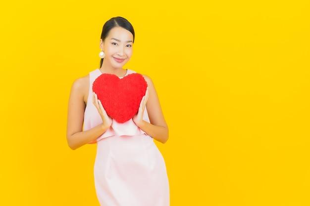 Glimlach van de portret de mooie jonge aziatische vrouw met de vorm van het harthoofdkussen op geel