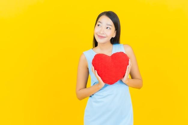 Glimlach van de portret de mooie jonge aziatische vrouw met de vorm van het harthoofdkussen op gele kleurenmuur