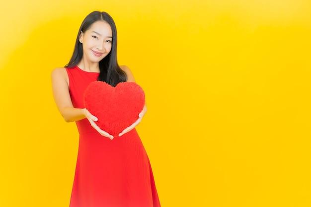 Glimlach van de portret de mooie jonge aziatische vrouw met de vorm van het harthoofdkussen op gele muur