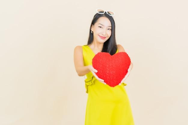 Glimlach van de portret de mooie jonge aziatische vrouw met de vorm van het harthoofdkussen op kleurenmuur