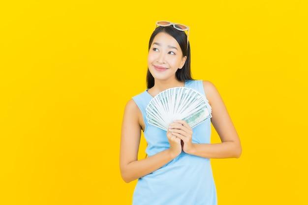 Glimlach van de portret de mooie jonge aziatische vrouw met heel wat contant geld en geld op gele kleurenmuur