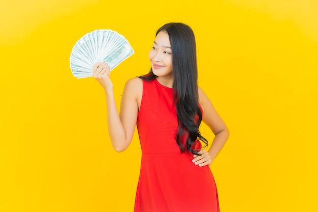 Glimlach van de portret de mooie jonge aziatische vrouw met heel wat contant geld en geld op gele muur