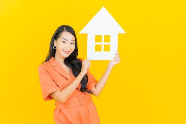 Glimlach van de portret de mooie jonge aziatische vrouw met het karton van het huisteken op geel