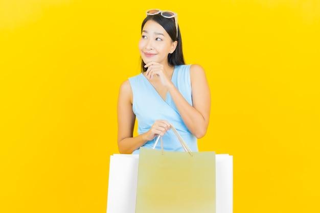 Glimlach van de portret de mooie jonge aziatische vrouw met het winkelen zak op gele kleurenmuur
