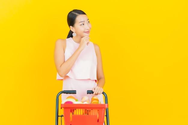 Glimlach van de portret de mooie jonge aziatische vrouw met kruidenierswinkelmandje van supermarkt op geel