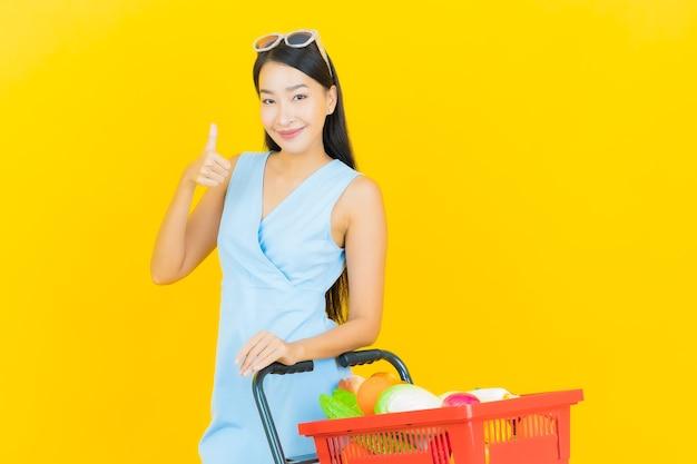Glimlach van de portret de mooie jonge aziatische vrouw met kruidenierswinkelmandje van supermarkt op gele kleurenmuur
