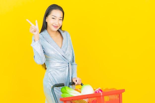 Glimlach van de portret de mooie jonge aziatische vrouw met kruidenierswinkelmandje van supermarkt op gele muur