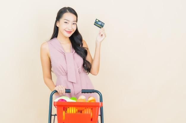 Glimlach van de portret de mooie jonge aziatische vrouw met kruidenierswinkelmandje van supermarkt