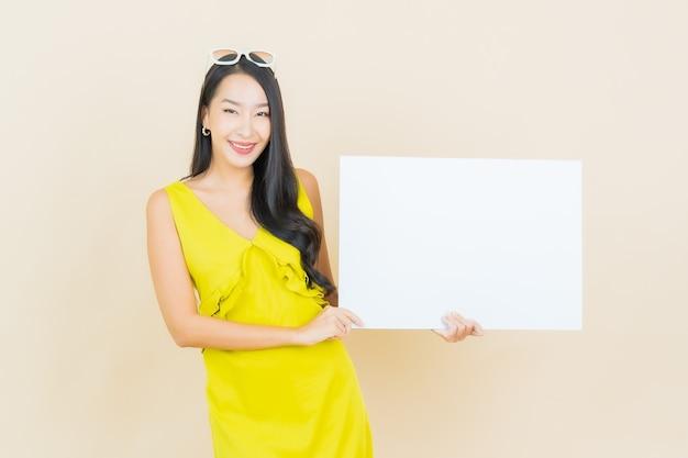 Glimlach van de portret de mooie jonge aziatische vrouw met leeg wit bord op gele muur
