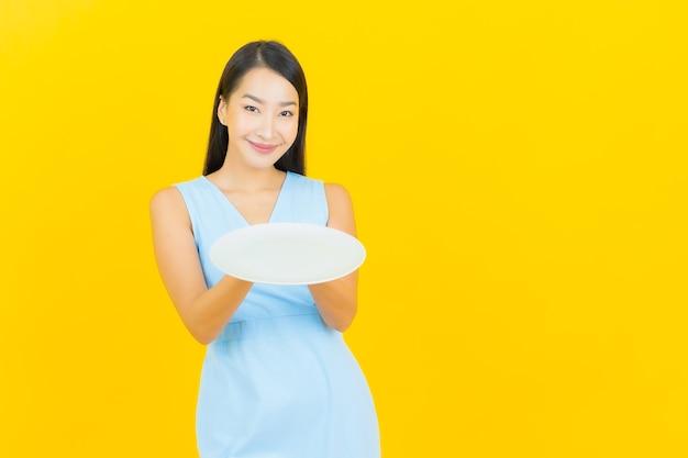 Glimlach van de portret de mooie jonge aziatische vrouw met lege plaatschotel op gele kleurenmuur