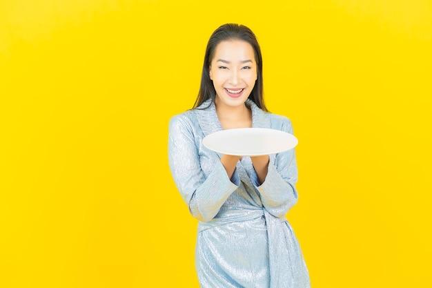 Glimlach van de portret de mooie jonge aziatische vrouw met lege plaatschotel op gele muur