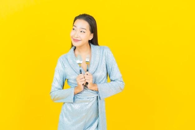 Glimlach van de portret de mooie jonge aziatische vrouw met lepel en vork op gele muur
