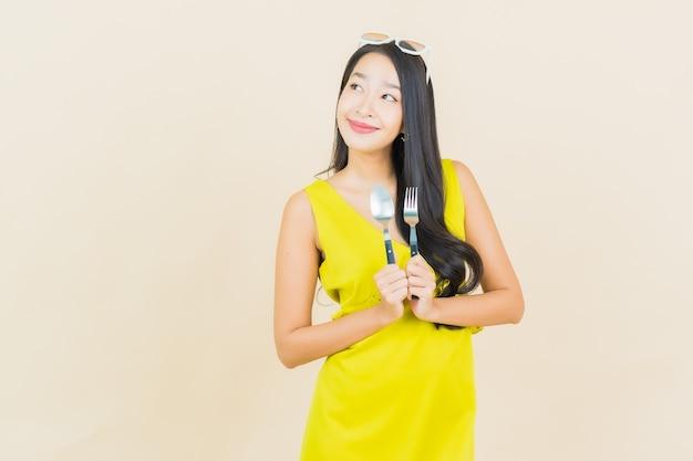 Glimlach van de portret de mooie jonge aziatische vrouw met lepel en vork op kleurenmuur