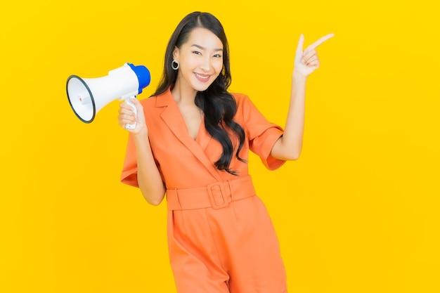 Glimlach van de portret de mooie jonge aziatische vrouw met megafoon op geel