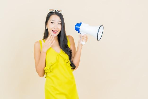 Glimlach van de portret de mooie jonge aziatische vrouw met megafoon op kleurenmuur