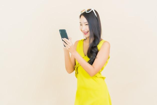 Glimlach van de portret de mooie jonge aziatische vrouw met slimme mobiele telefoon op kleurenmuur
